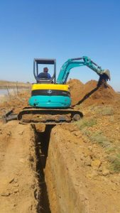 Kubota digging on both sides of the trenches